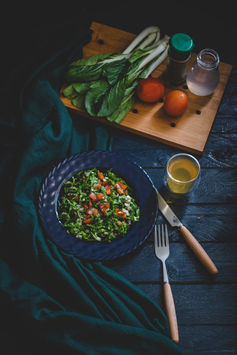 vegetable salad in bowl with fork, knife, and glass