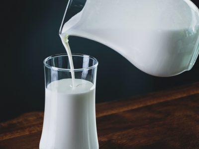 person pours milk into glass