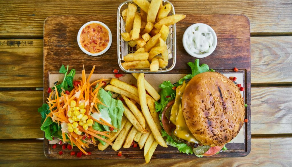 fries and burger on brown wooden tray