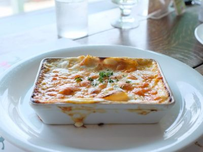 lasagna in bowl on plate beside half empty drinking glass